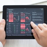 tablet, chart, ipad, man, bloomberg, business, stock, people, touch, hand, market, buy, course, app, notebook, schedule, bank, plastic, editorial, technology, computer, actions, mobile, currency, electronic, payment, purchase, background, device, online, statistic, exchange, shares, pay, holder, display, transaction, interface, illustrative, internet, commercial, finance, gadget, card, hold, e-commerce, macbook, money, terminal, apple, office, banking, wallet